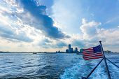 New Jersey city skyline from boat with American flag in New York US