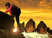 Girl on rock, in the background Tre Cime di Lavaredo at sunset ,Dolomite Alps, Italy