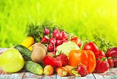 Fruits and vegetables on wooden table and field with green grass on background