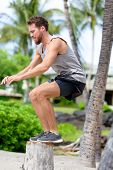 Fitness athlete bench jump squat jumping outside in nature landscape. Strength training fit male working out exercising outdoors on beach in summer doing jumping on tree trunk.