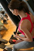 Woman in fitness club exercising on rowing machine