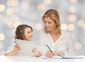 people, family, home education, children and technology concept - happy mother and daughter with tablet pc and notebook over holidays lights background