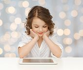 people, technology, education and children concept - happy smiling girl with tablet pc computer over holidays lights background