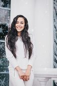 Young beautiful woman in sweater standing under the snowfall