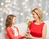 people, holidays, relations and family concept - happy little daughter giving flowers to her mother over holidays lights background