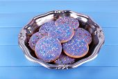 Group of glazed cookies in metal bowl on color wooden planks background