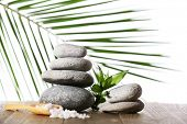 Stack of spa stones with spoon of sea salt on wooden surface isolated on white