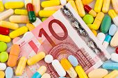euro banknotes and tablets, symbol photo for costs of medicines and health insurance