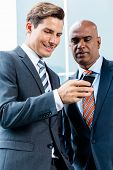 Indian and Caucasian business man looking at smart phone reading text
