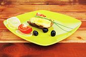 fish fillet with greek olives,tomatoes,chives and lemon over wood