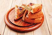 baked food : apple pie cuts on wooden plate over table with cinnamon sticks