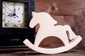 Retro clock with decorative horse on table on wooden background