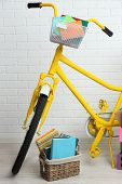 Bicycle with books in basket on brick wall background