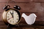 Retro clock with decorative bird on table on wooden background
