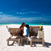 Couple relax on a tropical beach at Maldives