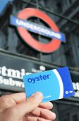 LONDON, UK - JANUARY 19: A young man holds an Oyster card at the entrance of the Underground on January 19, 2015 in London, United Kingdom. This card is used on public transport in Greater London