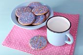 Plate of glazed cookies and mug of milk on napkin and color wooden table background
