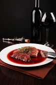 Grilled steak in wine sauce with glass of wine on dark background