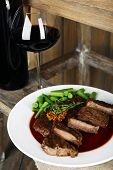 Steak with wine sauce on plate and bottle of wine on wooden background