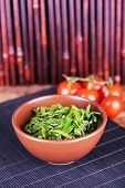 Seaweed salad in bowl with cherry tomatoes on bamboo mat background