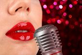 Woman with red lips and retro microphone on night lights background, karaoke concept