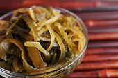Seaweed in glass bowl on bamboo mat background
