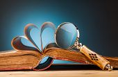Old Book  And Magnifying Glass On Wooden Table