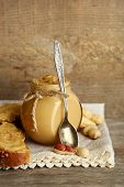 Fresh peanut butter in jar on wooden background
