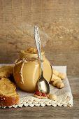 Fresh peanut butter in jar on wooden background