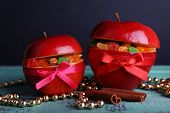 Christmas red apples stuffed with dried fruits on color wooden table and dark background