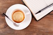 Cup of coffee on saucer with diary, pen and spoon on wooden table background