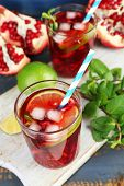 Pomegranate drink in glasses with slices of lime and mint on color wooden background