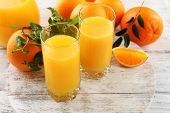 Glass of orange juice and oranges on color wooden table background