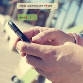 a young man sending a text message with a smartphone with the text Happy valentines day, I love you