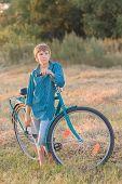Teenager Boy Holding Bike In Farm Field