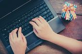 Hands Typing On Laptop And Gift On Wooden Background