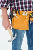 Close-up of male repairman wearing tool belt while holding hammer on white background