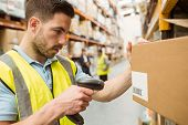 image of warehouse  - Warehouse worker scanning barcodes on boxes in a large warehouse - JPG