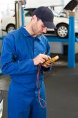 Mechanic using a diagnostic tool at the repair garage