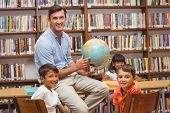 Cute pupils and teacher looking at globe in library at the elementary school