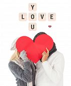 Couple in winter fashion posing with heart shape against love you tiles