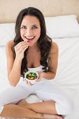 Pretty brunette eating candy in bed at home in bedroom