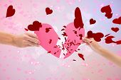 Hands holding two halves of broken heart against digitally generated girly heart design