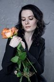 Stylish beautiful young woman with orange roses in hands