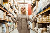 Smiling female manager showing with her hands in a large warehouse
