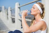 Fit blonde sitting on the pier drinking water on a sunny day