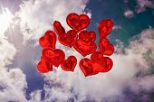 Composite image of heart balloons in the sky
