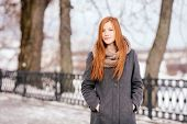stock photo of stroll  - Winter portrait of a cute redhead lady in grey coat and scarf strolling in the park - JPG