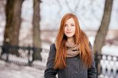 Winter portrait of a cute redhead lady in grey coat and scarf posing in the park