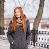 Winter portrait of a cute redhead lady in grey coat and scarf strolling in the park